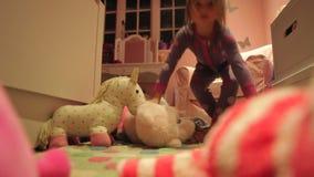 Παιχνίδι κοριτσιών με τα παιχνίδια στην κρεβατοκάμαρα που φορά τις πυτζάμες απόθεμα βίντεο