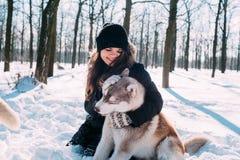 Παιχνίδι κοριτσιών με τα σκυλιά στο χιόνι Στοκ φωτογραφία με δικαίωμα ελεύθερης χρήσης