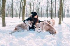 Παιχνίδι κοριτσιών με τα σκυλιά στο χιόνι Στοκ φωτογραφίες με δικαίωμα ελεύθερης χρήσης