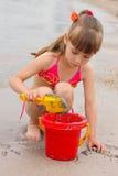 Παιχνίδι κοριτσιών με την άμμο στην ακροθαλασσιά Στοκ εικόνες με δικαίωμα ελεύθερης χρήσης