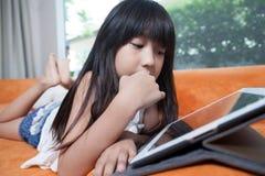 Παιχνίδι κοριτσιών με την ταμπλέτα Στοκ Φωτογραφίες