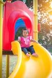 Παιχνίδι κοριτσιών μικρών παιδιών σε μια φωτογραφική διαφάνεια στην παιδική χαρά παιδιών Στοκ Εικόνα