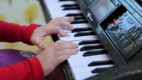 Παιχνίδι κοριτσιών σε ένα πιάνο παιχνιδιών, κινηματογράφηση σε πρώτο πλάνο απόθεμα βίντεο