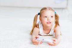 Παιχνίδι κοριτσιών σε μια κονσόλα παιχνιδιών στοκ εικόνες