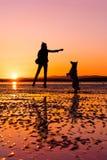 Παιχνίδι κοριτσιών Hipster με το σκυλί σε μια παραλία κατά τη διάρκεια του ηλιοβασιλέματος, σκιαγραφίες Στοκ εικόνες με δικαίωμα ελεύθερης χρήσης