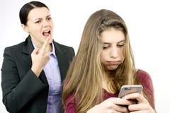 Παιχνίδι κορών με το τηλέφωνο κυττάρων ενώ η μητέρα φωνάζει Στοκ φωτογραφία με δικαίωμα ελεύθερης χρήσης