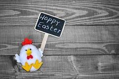 Παιχνίδι κοτόπουλου που κρατά το ευτυχές κείμενο Πάσχας Στοκ φωτογραφίες με δικαίωμα ελεύθερης χρήσης