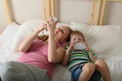 Παιχνίδι μητέρων και γιων με τα τηλέφωνα Στοκ φωτογραφίες με δικαίωμα ελεύθερης χρήσης