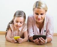 Παιχνίδι μητέρων και κοριτσιών με τα κινητά τηλέφωνα εσωτερικά Στοκ εικόνα με δικαίωμα ελεύθερης χρήσης