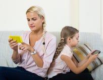 Παιχνίδι μητέρων και κοριτσιών με τα κινητά τηλέφωνα εσωτερικά Στοκ Φωτογραφίες