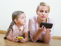 Παιχνίδι μητέρων και κοριτσιών με τα κινητά τηλέφωνα εσωτερικά Στοκ Εικόνες