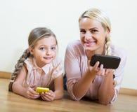 Παιχνίδι μητέρων και κοριτσιών με τα κινητά τηλέφωνα εσωτερικά Στοκ Φωτογραφία