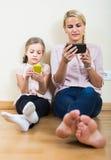 Παιχνίδι μητέρων και κοριτσιών με τα κινητά τηλέφωνα εσωτερικά Στοκ Εικόνα
