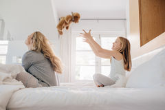 Παιχνίδι μητέρων και κορών με τη teddy αρκούδα στο κρεβάτι Στοκ Εικόνες