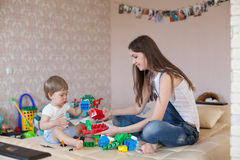Παιχνίδι μητέρων και μικρών παιδιών με τα παιχνίδια στο βρεφικό σταθμό Στοκ Εικόνα