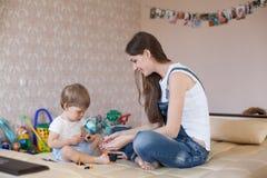 Παιχνίδι μητέρων και μικρών παιδιών με τα παιχνίδια στο βρεφικό σταθμό Στοκ εικόνα με δικαίωμα ελεύθερης χρήσης
