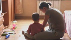 Παιχνίδι μητέρων και παιδιών στη συνεδρίαση δωματίων στο πάτωμα απόθεμα βίντεο