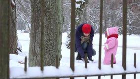Παιχνίδι μητέρων με λίγη κόρη μωρών με το χιόνι το χειμώνα 4K απόθεμα βίντεο