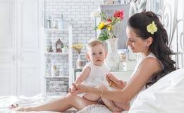 Παιχνίδι μητέρων με μια χρονών κόρη στο κρεβάτι Στοκ φωτογραφία με δικαίωμα ελεύθερης χρήσης