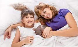 Παιχνίδι μητέρων με την κόρη στο κρεβάτι Στοκ φωτογραφία με δικαίωμα ελεύθερης χρήσης