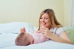 Παιχνίδι μητέρων με το μωρό της στο κρεβάτι Χαμόγελα Mom στο παιδί της Στοκ Φωτογραφίες