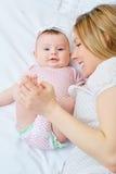 Παιχνίδι μητέρων με το μωρό της στο κρεβάτι Χαμόγελα Mom στο παιδί της Στοκ Εικόνα