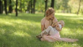 Παιχνίδι μητέρων με το παιδί της σε ένα πάρκο στη χλόη φιλμ μικρού μήκους