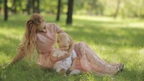 Παιχνίδι μητέρων με το παιδί της σε ένα πάρκο στη χλόη απόθεμα βίντεο