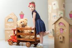 Παιχνίδι μικρών κοριτσιών με ένα μεγάλο ξύλινο αυτοκίνητο Στοκ φωτογραφία με δικαίωμα ελεύθερης χρήσης