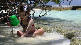 Παιχνίδι μικρών κοριτσιών με τα κύματα θάλασσας σε μια τροπική παραλία κίνηση αργή απόθεμα βίντεο
