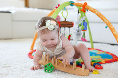Παιχνίδι μικρών κοριτσιών με τα παιχνίδια στο σπίτι στο πάτωμα Στοκ Εικόνα