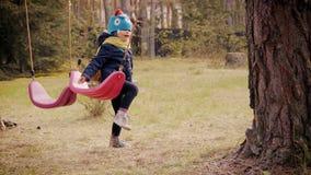 Παιχνίδι μικρών κοριτσιών με την ταλάντευση στο δάσος απόθεμα βίντεο