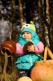 Παιχνίδι μικρών κοριτσιών με τις κολοκύθες στη φύση φθινοπώρου Στοκ Εικόνες