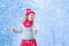 Παιχνίδι μικρών κοριτσιών με τις νιφάδες χιονιού παιχνιδιών στο χειμερινό πάρκο Στοκ Φωτογραφία