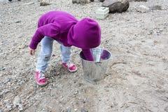 Παιχνίδι μικρών κοριτσιών με τους βράχους Στοκ Εικόνα