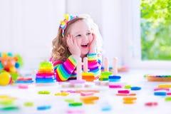 Παιχνίδι μικρών κοριτσιών με τους ξύλινους φραγμούς παιχνιδιών Στοκ φωτογραφία με δικαίωμα ελεύθερης χρήσης