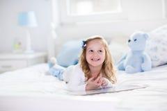 Παιχνίδι μικρών κοριτσιών με το παιχνίδι και ανάγνωση ενός βιβλίου στο κρεβάτι Στοκ Εικόνα
