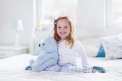 Παιχνίδι μικρών κοριτσιών με το παιχνίδι και ανάγνωση ενός βιβλίου στο κρεβάτι Στοκ φωτογραφία με δικαίωμα ελεύθερης χρήσης
