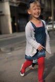 Παιχνίδι μικρών κοριτσιών στην οδό και χαμόγελο Στοκ φωτογραφία με δικαίωμα ελεύθερης χρήσης
