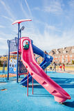 Παιχνίδι μικρών κοριτσιών στην υψηλή φωτογραφική διαφάνεια στην παιδική χαρά παιδιών Στοκ Εικόνες