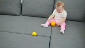 Παιχνίδι μικρών κοριτσιών στον καναπέ στο καθιστικό απόθεμα βίντεο
