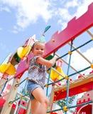 Παιχνίδι μικρών κοριτσιών χαμόγελου στον εξοπλισμό παιδικών χαρών Στοκ Εικόνα
