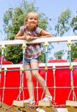 Παιχνίδι μικρών κοριτσιών χαμόγελου στον εξοπλισμό παιδικών χαρών Στοκ εικόνες με δικαίωμα ελεύθερης χρήσης