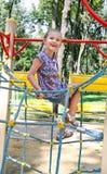 Παιχνίδι μικρών κοριτσιών χαμόγελου στον εξοπλισμό παιδικών χαρών Στοκ εικόνα με δικαίωμα ελεύθερης χρήσης
