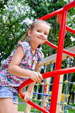 Παιχνίδι μικρών κοριτσιών χαμόγελου στον εξοπλισμό παιδικών χαρών Στοκ Εικόνες
