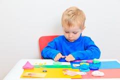 Παιχνίδι μικρών παιδιών με τη ζύμη αργίλου Στοκ φωτογραφία με δικαίωμα ελεύθερης χρήσης