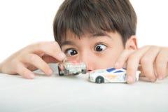 Παιχνίδι μικρών παιδιών με το παιχνίδι αυτοκινήτων στον πίνακα μόνο Στοκ Εικόνες