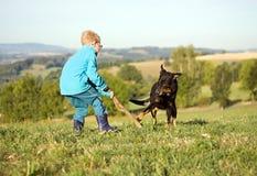 Παιχνίδι μικρών παιδιών με το σκυλί Στοκ Φωτογραφία
