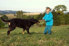 Παιχνίδι μικρών παιδιών με το σκυλί Στοκ φωτογραφία με δικαίωμα ελεύθερης χρήσης