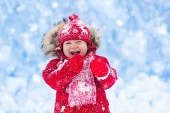 Παιχνίδι μωρών με το χιόνι το χειμώνα Στοκ φωτογραφία με δικαίωμα ελεύθερης χρήσης